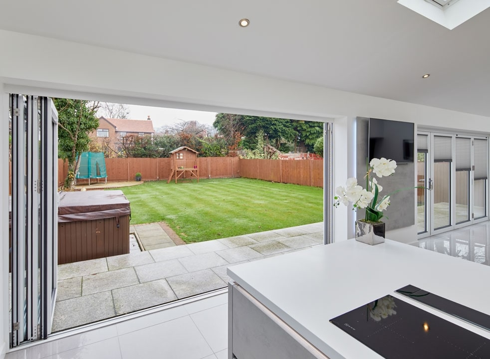 Open Supreme 3.6M White aluminium Bifold doors shows garden view