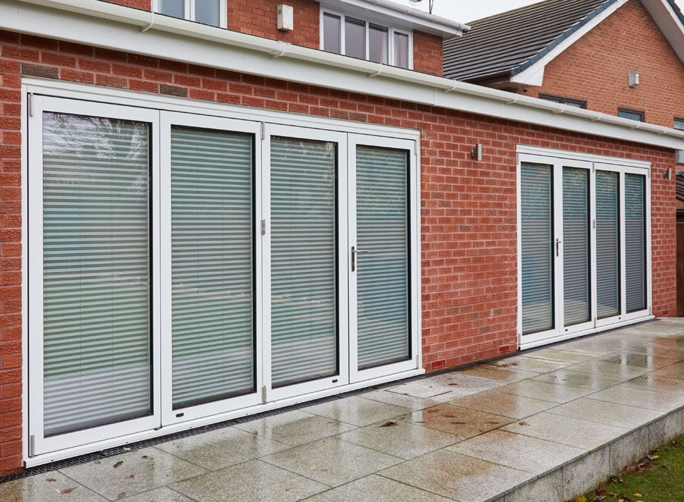 Blinds down and closed Supreme 3.6M White aluminium Bifold doors view from the garden