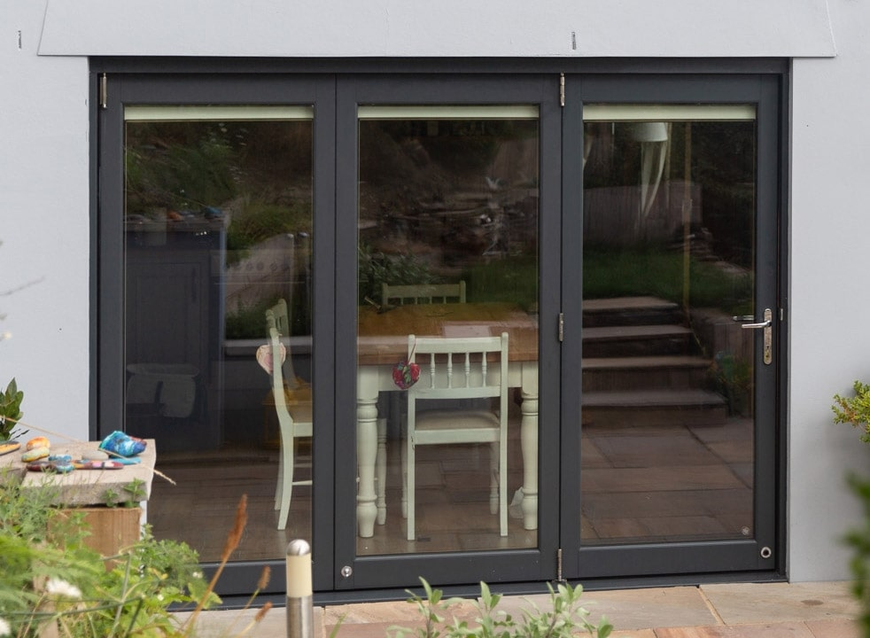 Outside closed Ultra 2.7M grey bifold doors with a view into the kitchen