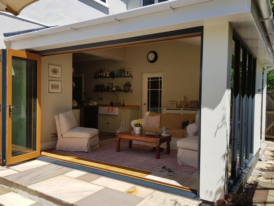 Outside view, open Ultra Grey 3.6M bifold doors and Ultra bespoke window