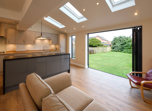 Open Status Aluminium grey bifold doors and window from the inside looking out