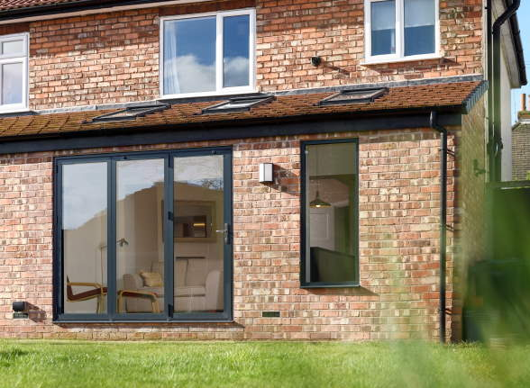 Closed Status Aluminium grey bifold doors and window from the outside
