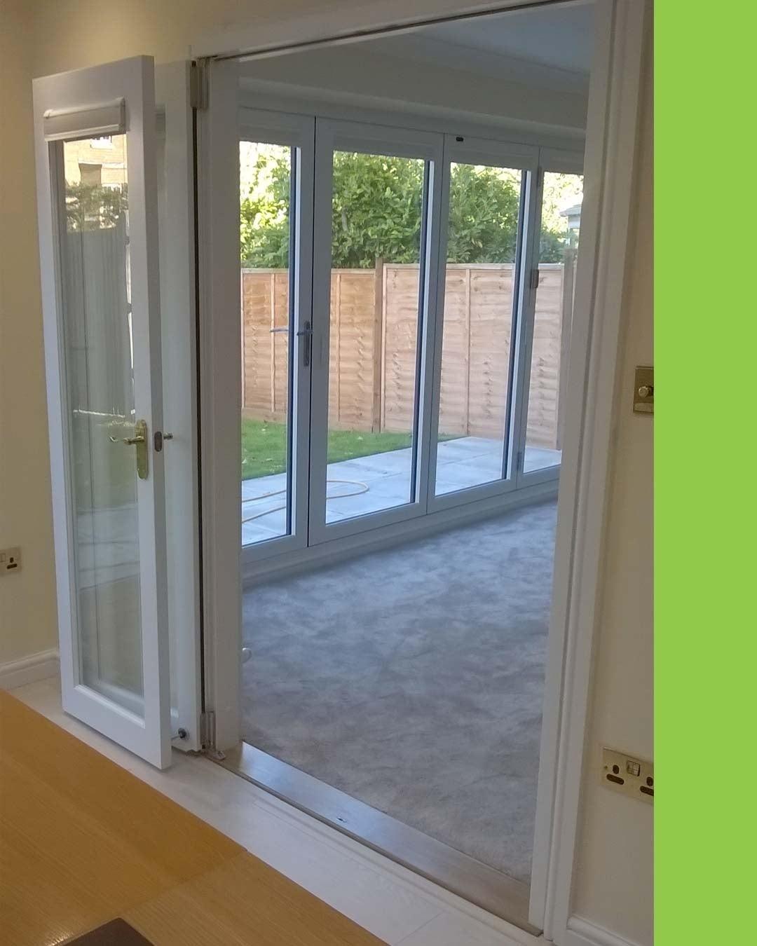 Inspire bifold doors open with a view of Supreme white aluminium external bifold doors